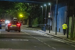 © Licensed to London News Pictures. 26/06/2020. London, UK. A police officer walks towards two vehicles inside the cordon. A person has been stabbed on Du Cane Road in East Acton on Thursday 25th June 2020. A cordon closed off a large section of the road underneath a railway bridge where two vehicles remained. Photo credit: Peter Manning/LNP