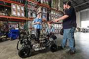 01/14/2016 133401 -- Garland, TX -- &copy; Copyright 2016 Mark C. Greenberg<br /> <br /> From left: President and COO Rick Sukkar and CEO Alex Keechleof talk with warehouse manager Kevin Sadler in the warehouse of Garland, Texas based Monster Moto