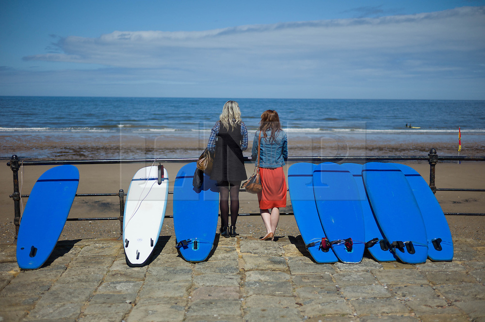 © Licensed to London News Pictures. 01/06/2013<br /> <br /> Saltburn Beach, Cleveland, Untied Kingdom<br /> <br /> On the first day of summer two girls watch the surf as they visit Saltburn to enjoy the warm weather.<br /> <br /> <br /> Photo credit : Ian Forsyth/LNP© Licensed to London News Pictures.