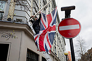 Alongside a No Entry traffic sign, the British Union Jack flag is unfurled by a workman up some ladders outside a West End hotel located on the corner of Monmouth Street in Soho, on 3rd March 2020, in London, England.