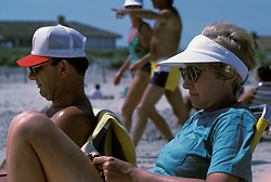 Couple relaxing, reading and tanning on the beach.  Stone Harbor, NJ.