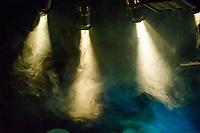 Stage lights shine through smoke.