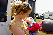 A woman holds a sleeping baby in the campsite, Boomtown, Matterley Estate, Alresford Road, near Winchester, Hampshire, UK, August, 2010