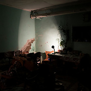 A single desk lamp illuminates a room of one of the many bomb shelters around Donetsk.