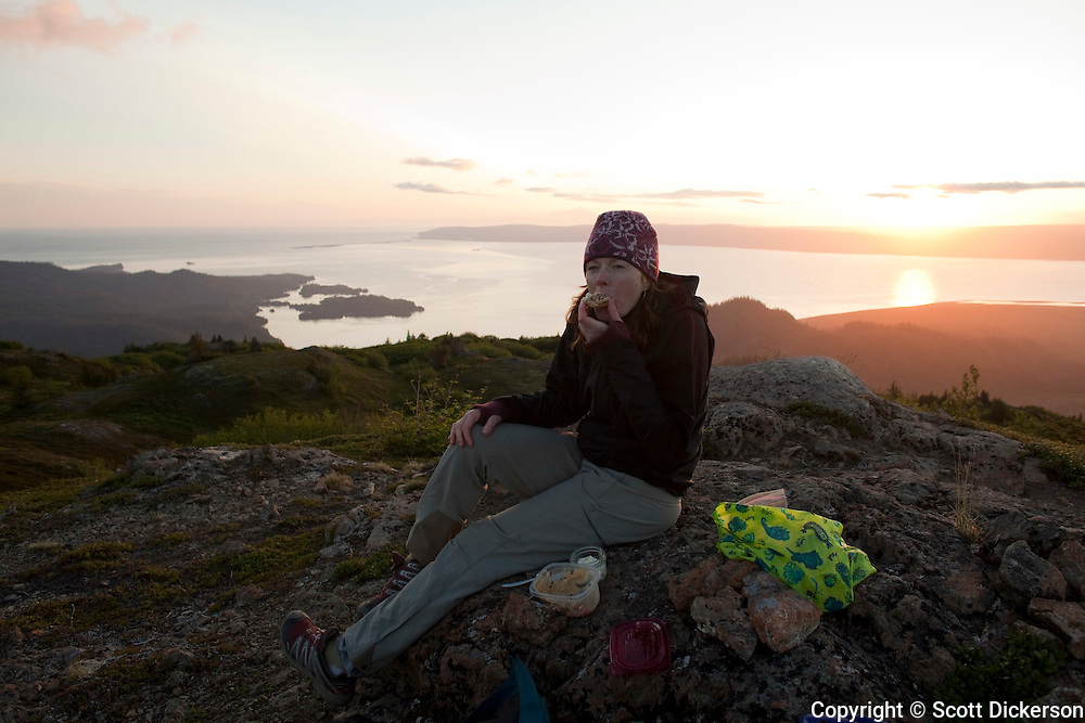 Stephanie Haynes having a snack while hiking on the Alpine Ridge trail in Kachemak Bay State Park, near Homer, Alaska. Halibut Cover, Homer and the Homer Spit are in the background across Kachemak Bay.