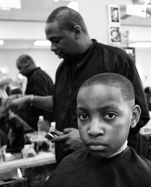 a customer waits for Vernon Anthony to finish cutting his hair at Andrews One Barber Shop in Clinton Maryland, works on a customers hair, March 19, 2011  Photo by Cooper Evans