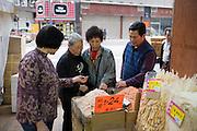 Women shopping for Chinese dried fish and medicines in shop in Wing Lok Street, Sheung Wan, Hong Kong, China