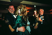 Two gay men dancing with bridesmaids at a wedding