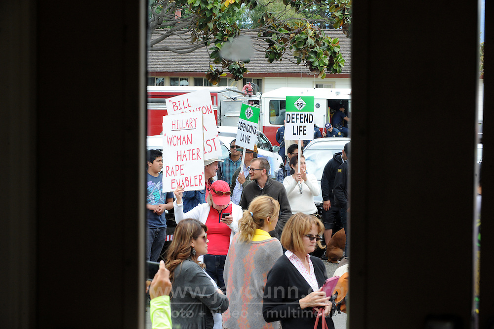 Protesters seen through the glass inside Hartnell College during presidential candidate Hillary Clinton's visit on Wednesday, May 25th, 2016.