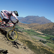 Bryn Dickerson from Wellington in action during the NZBNZ South Island Downhill Cup mountain bike downhill series held on The Remarkables face with a stunning backdrop of the Wakatipu Basin. 150 riders took part in the two day event.  Queenstown, Otago, New Zealand. 9th January 2012. Photo Tim Clayton