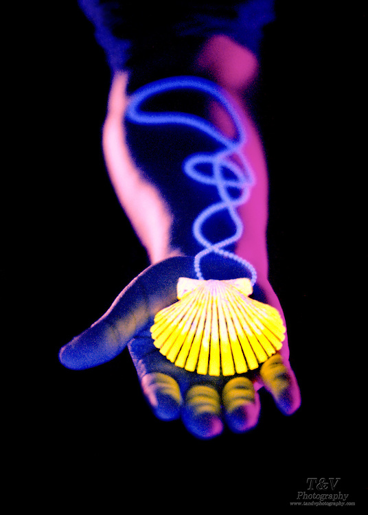 Arm and hand with glowing chain and shell.Black light