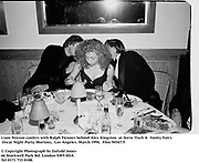 Liam Neeson confers with Ralph Fiennes behind Alex Kingston  at Steve Tisch &  Vanity Fair's Oscar Night Party,<br />Mortons,  Los Angeles. March 1994.  Film 94567/5<br /> <br />© Copyright Photograph by Dafydd Jones<br />66 Stockwell Park Rd. London SW9 0DA<br />Tel 0171 733 0108.