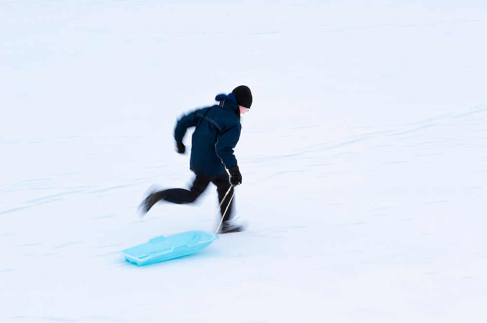 Boy running with sledge in the snow