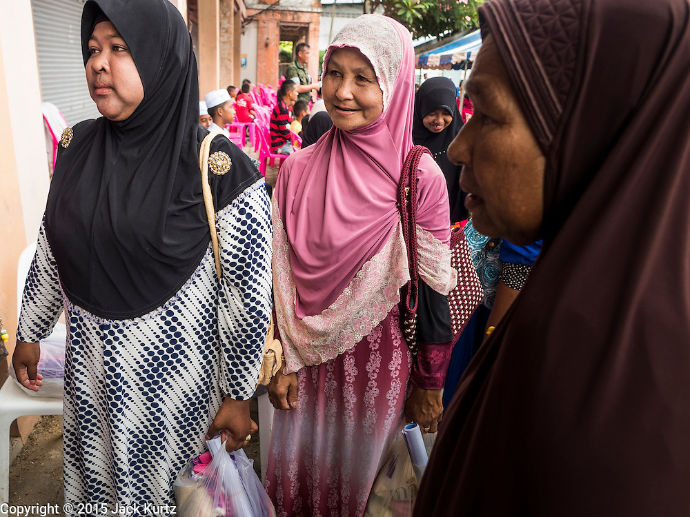 14 JUNE 2015 - NARATHIWAT, NARATHIWAT, THAILAND:  Thai Muslim woment wait to talk to Thai army medics during a food distribution event in Narathiwat. The food distribution happens every year before Ramadan, which starts June 18. The annual food distribution event is organized by the Southern Peace Media Club, a group of Thai journalists who work in the southern provinces of Pattani, Narathiwat and Yala. An insurgency pitting Muslim extremists against the Thai government has rocked Thailand's southern three provinces since 2001. More than 6,000 people have been killed in the sectarian violence.   PHOTO BY JACK KURTZ