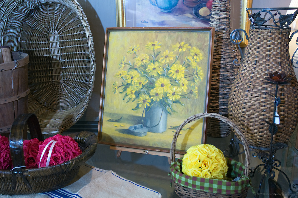 """Keller likes to feature the work of local artists, including his aunt, Nancy Lee Holderman of New Albany. Her original oil painting from 1976, """"Artichoke Blooms,"""" is for sale in the store along with more recent works. Gregg Keller, owner of Rellek Fine Consignment and Home Furnishings, located at 817 E. Market St. in NuLu area of Louisville, Ky. (Photo by Brian Bohannon)"""