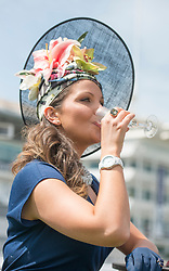 TODAY PICTURE © Licensed to London News Pictures. 06/06/2014. Epsom, UK. Rachel Hanson 27, from Epsom, wears her self made hat which took her three days to complete.   Ladies Day today 6th June 2014 at Epsom 2014 Investic Derby Festival in Surrey. Traditionally, elegant, fashionable racegoers gather for a classic day's racing at Epsom Racecourse, Surrey. Photo credit : Stephen Simpson/LNP