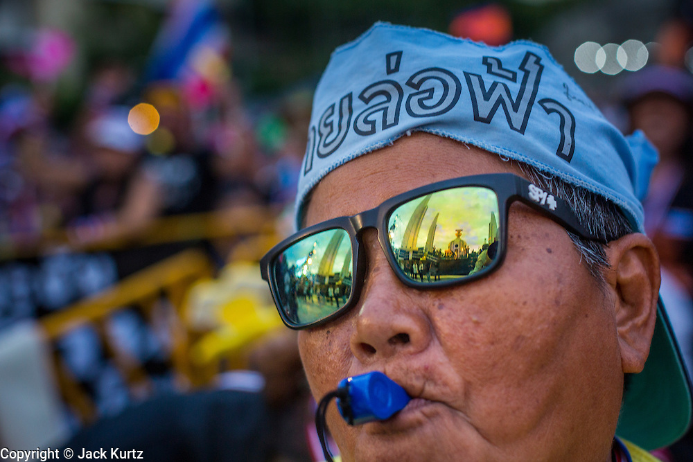 """15 NOVEMBER 2013 - BANGKOK, THAILAND: Democracy Monument, the center of anti-government protests in Bangkok, is reflected in the sunglasses of a woman at the protest. Tens of thousands of Thais packed the area around Democracy Monument in the old part of Bangkok Friday night to protest against efforts by the ruling Pheu Thai party to pass an amnesty bill that could lead to the return of former Prime Minister Thaksin Shinawatra. Protest leader and former Deputy Prime Minister Suthep Thaugsuban announced an all-out drive to eradicate the """"Thaksin regime."""" The protest Friday was the biggest since the amnesty bill issue percolated back into the public consciousness. The anti-government protesters have vowed to continue their protests even though the Thai Senate voted down the bill, thus killing it for at least six months.     PHOTO BY JACK KURTZ"""