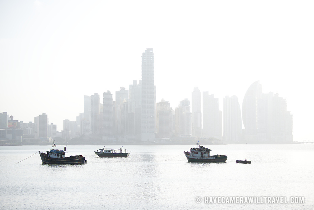 Silhouette of wooden fishing boats at anchor on the waterfront of Panama City, Panama, on Panama Bay, with the skyscrapers of Punta Paitilla in the background on a hazy morning.