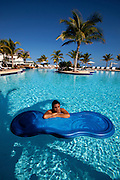 Exotic woman on float in blue tropical swimming pool with deep blue sky