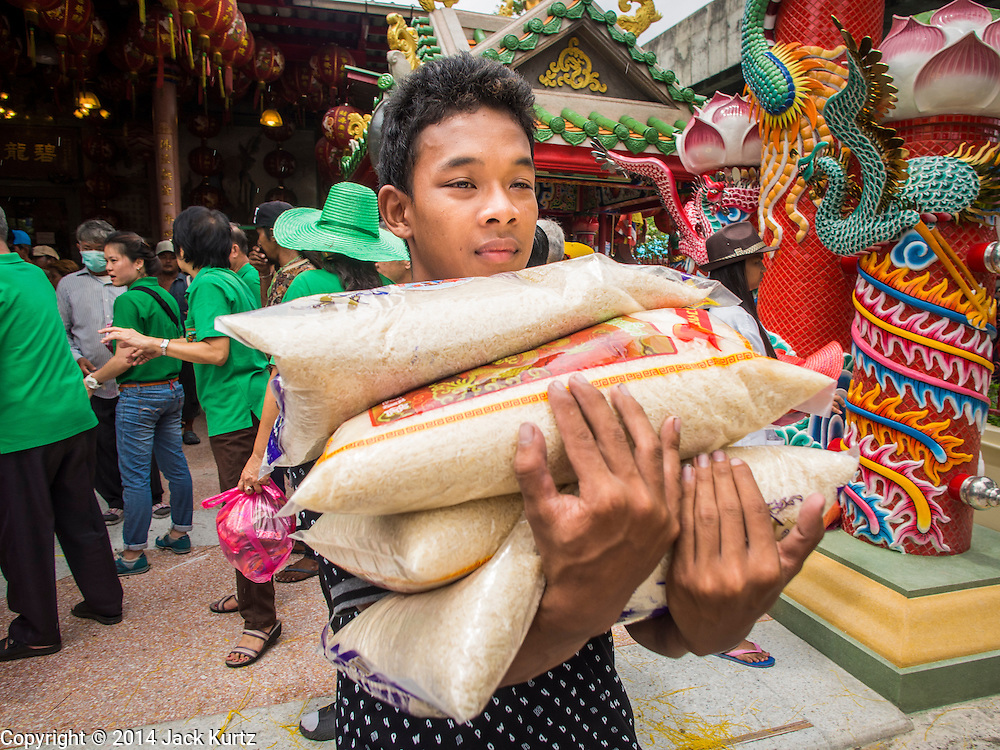 """07 AUGUST 2014 - BANGKOK, THAILAND:   A man carries sacks of rice away from a food distribution at Pek Leng Keng Mangkorn Khiew Shrine in Bangkok. Thousands of people lined up for food distribution at the Pek Leng Keng Mangkorn Khiew Shrine in the Khlong Toei section of Bangkok Thursday. Khlong Toei is one of the poorest sections of Bangkok. The seventh month of the Chinese Lunar calendar is called """"Ghost Month"""" during which ghosts and spirits, including those of the deceased ancestors, come out from the lower realm. It is common for Chinese people to make merit during the month by burning """"hell money"""" and presenting food to the ghosts. At Chinese temples in Thailand, it is also customary to give food to the poorer people in the community.      PHOTO BY JACK KURTZ"""