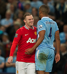 MANCHESTER, ENGLAND - Monday, April 30, 2012: Manchester City's Vincent Kompany shares a laugh with Manchester United's Wayne Rooney during the Premiership match at the City of Manchester Stadium. (Pic by Chris Brunskill/Propaganda)