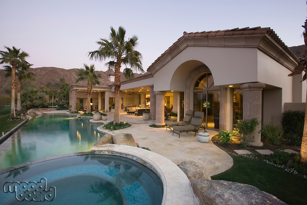 Luxury swimming pool and house exterior at dusk