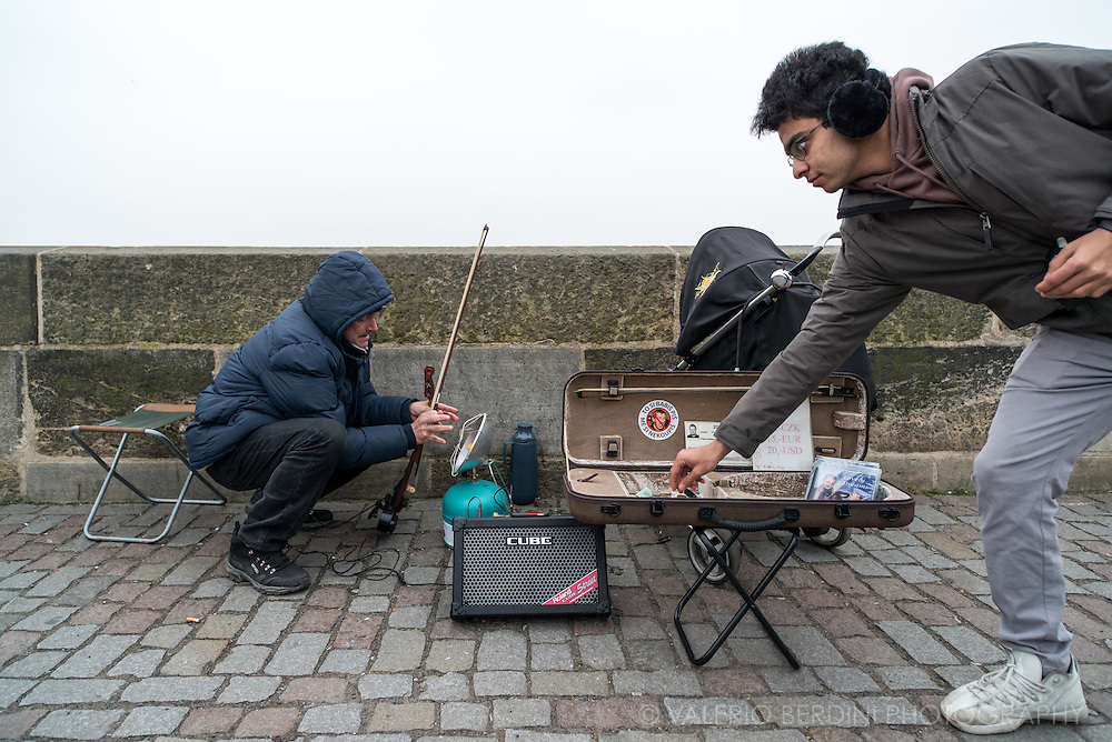 A violinist on Charles Bridge warms up hands to be able to play the instruments for passers-by
