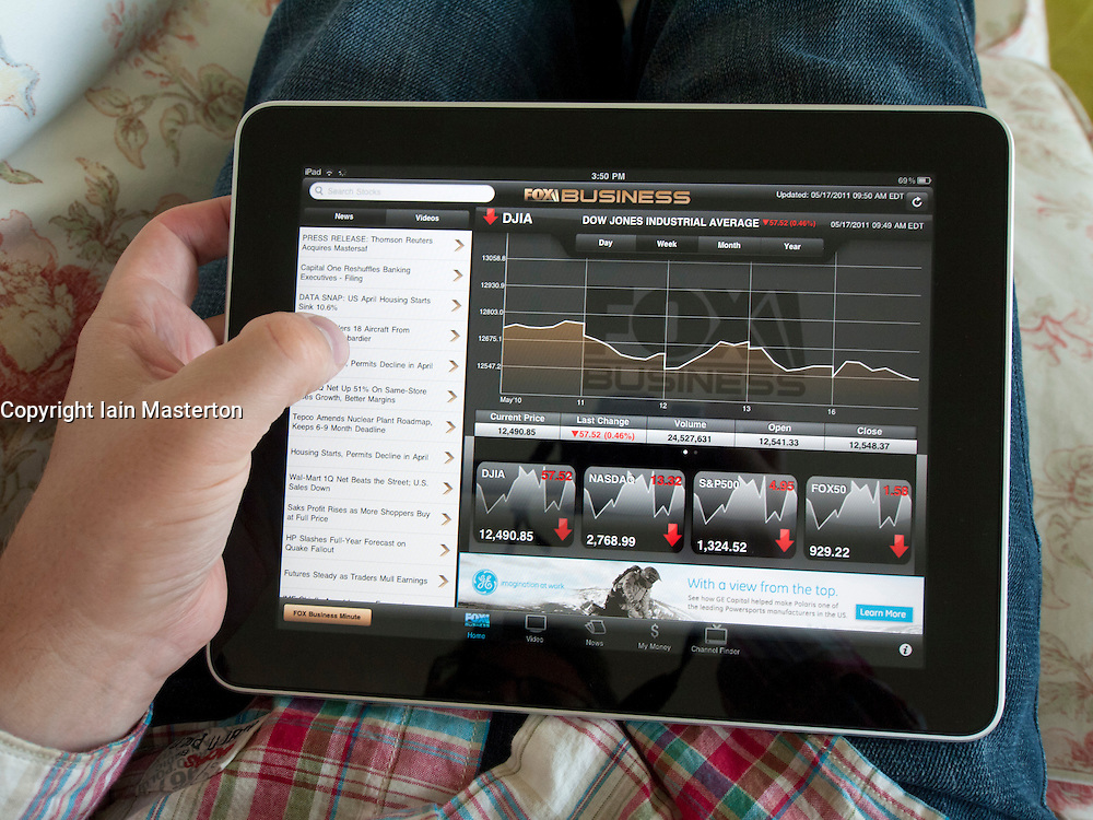 Man checking stock market performance using Fox Business app on an iPad touch screen tablet computer