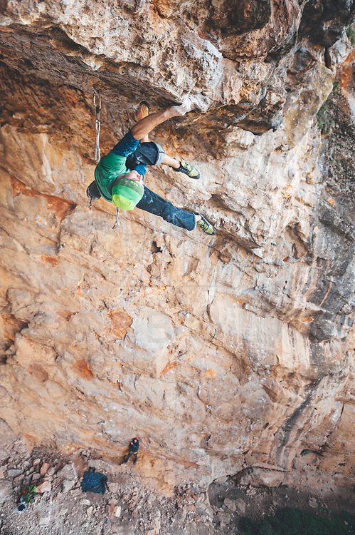Climber climbing on a limestone roof cave in Somaen, Spain