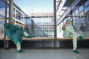 two surgeons in hospital corridor using mobile phones
