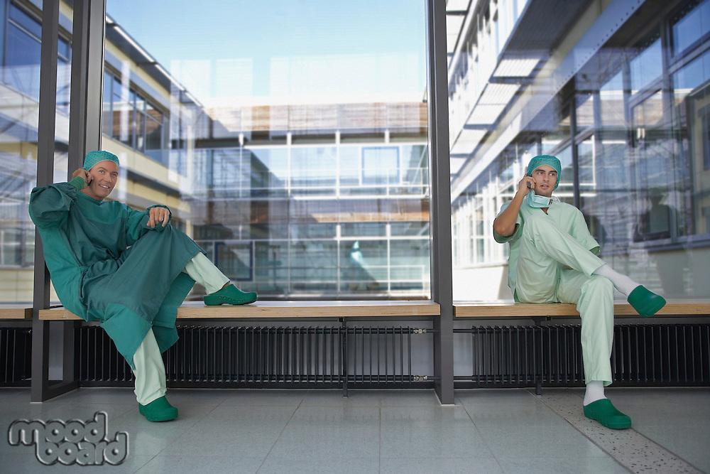 two surgeons in hospital corridor using mobile phones