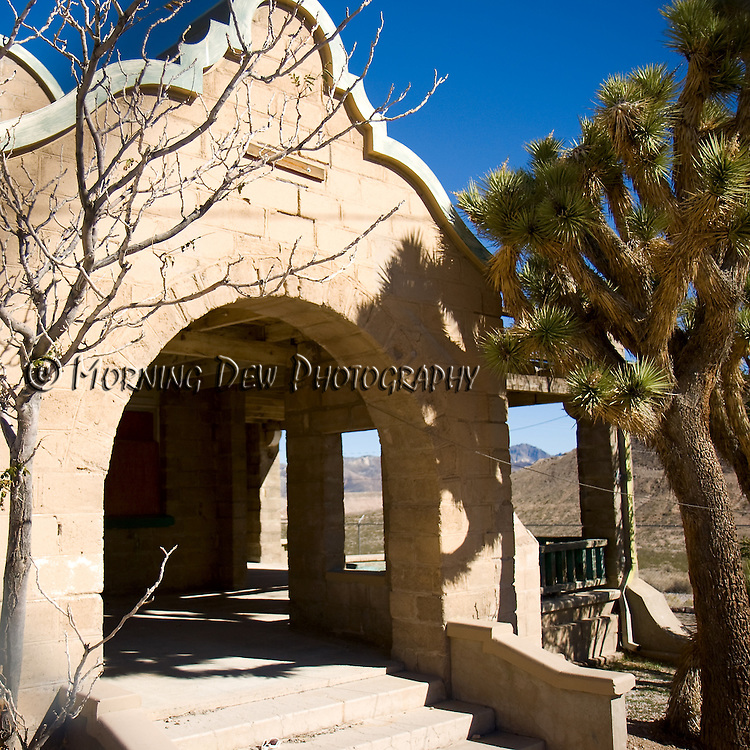 A joshua tree grows alongside the arched entrance to Rhyolite's old train station.