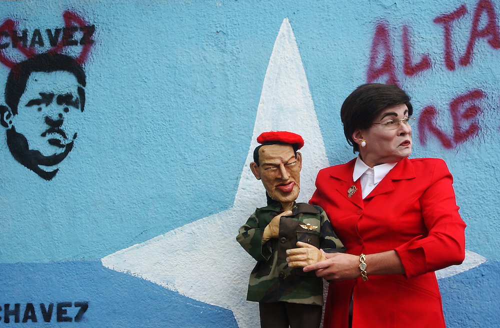 Gilberto Gonzalez, comic and political satirist, stands for a portrait in front of graffiti in Chavista part of town.  He is in costume as a Venezuela media personality. Gonzales was at the center of an uproar last year when he performed his politically charged show, which contains a skit with a Hugo Chavez puppet(shown) at a US Embassy party.     With Venezuela entrenched in a bitter fight over the upcoming presidential referendum that has divided the country,many political satirists have taken center stage in the Venezuelan world of comedy.