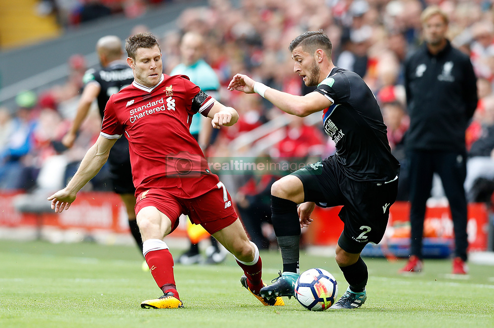 Liverpool's James Milner and Crystal Palace's Joel Ward battle for the ball during the Premier League match at Anfield, Liverpool.