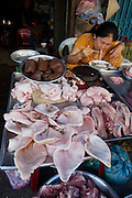 Cholon (Chinatown). Binh Tay Market. Pigs meat vendor having a Pho (noodle soup) for breakfast.