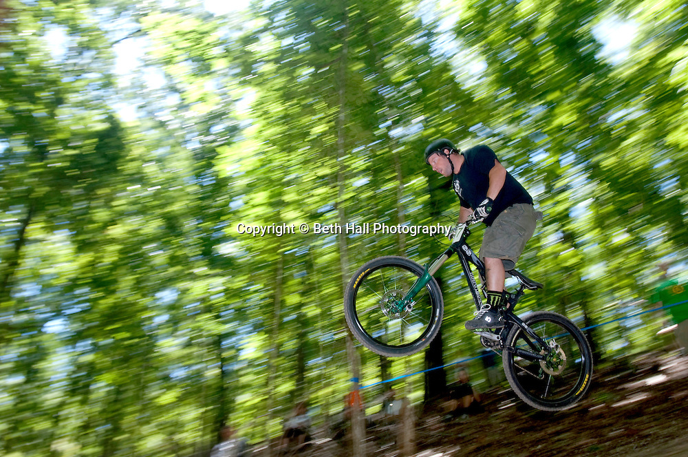 A competitor makes a jump during a the downhill race of a mountain bike competition