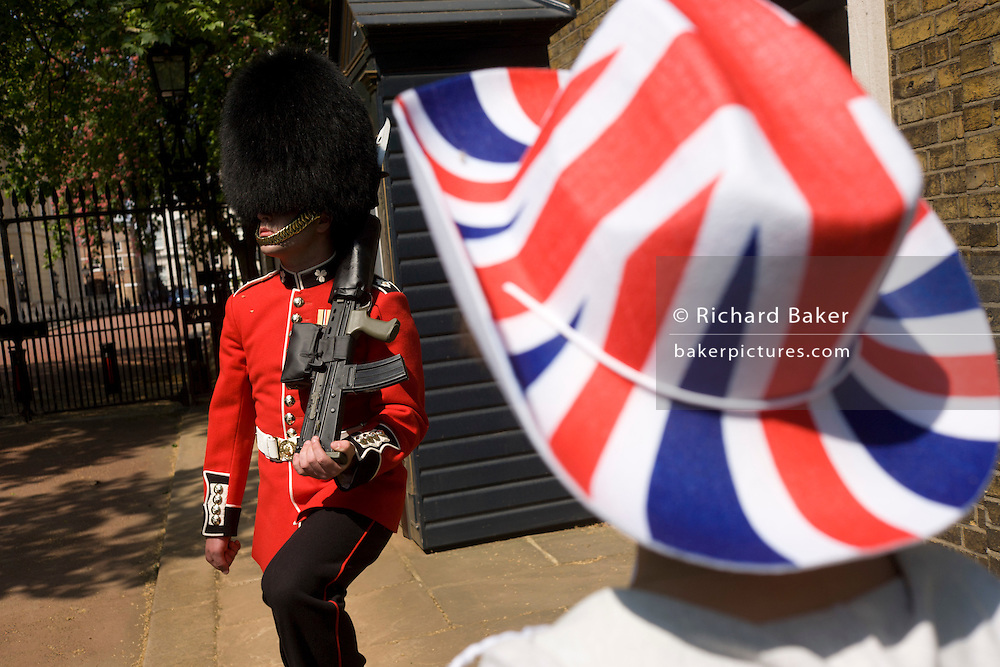24 hours before the royal marriage of Prince William and Kate Middleton, a guardsman stands by his sentry box in front of Clarence House in St James Palace where the royal bride is staying. A lady royalist stands admiring the soldier in a bright Union Jack-coloured hat as the guardsman approaches in tandem with an unseen colleague. Taking place on Friday 30th April in front of millions of Britons and foreign tourists (many American), the crowds are already gathering to claim their ideal locations in the front rows along the procession route.