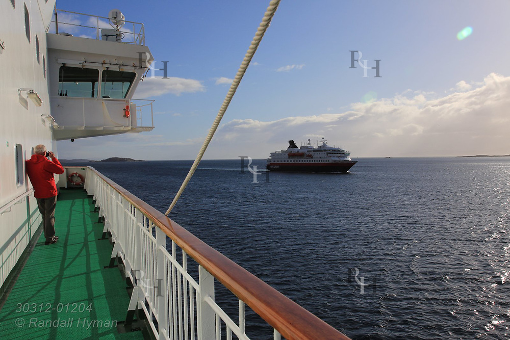Passenger aboard Hurtigruten cruise ship photographs passing sister ship in early May along north coast of Norway.