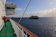 Passenger aboard Hurtigruten cruise ship photographs passing sister ship in early May along north coast of Norway.
