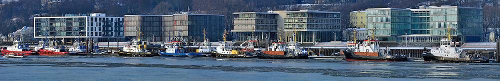 Schlepperbrücke Neumühlen in Hamburg im Winter. Eis treibt auf der Elbe.