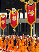 """22 FEBRUARY 2016 - KHLONG LUANG, PATHUM THANI, THAILAND:  Monks and novices file into the chedi before the evening service for Makha Bucha Day at Wat Phra Dhammakaya.  Makha Bucha Day is a public holiday in Cambodia, Laos, Myanmar and Thailand. Many people go to the temple to perform merit-making activities on Makha Bucha Day, which marks four important events in Buddhism: 1,250 disciples came to see the Buddha without being summoned, all of them were Arhantas, Enlightened Ones, and all were ordained by the Buddha himself. The Buddha gave those Arhantas the principles of Buddhism, called """"The ovadhapatimokha"""". Those principles are:  1) To cease from all evil, 2) To do what is good, 3) To cleanse one's mind. The Buddha delivered an important sermon on that day which laid down the principles of the Buddhist teachings. In Thailand, this teaching has been dubbed the """"Heart of Buddhism."""" Wat Phra Dhammakaya is the center of the Dhammakaya Movement, a Buddhist sect founded in the 1970s and led by Phra Dhammachayo.     PHOTO BY JACK KURTZ"""