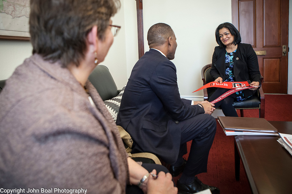 Representative Pramila Jayapal (D-WA, 7) receives a pennant of Seattle University from Isiaah Crawford, and Violet Boyer, left, of the National Association of Independent Colleges and Universities, on Tuesday, January 31, 2017.  This was the last of four 30-minute meetings with constituent advocacy groups during the day.  John Boal photo/for The Stranger