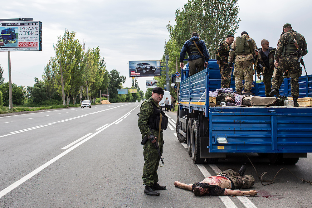 Members of the pro-Russia Vostok Battalion stand over the body of a pro-Ukrainian militia fighter on May 23, 2014 in Pisky, Ukraine. At least eight people between the two sides, including one civilian, were killed in an early morning firefight when the Donbass Battalion, a pro-Ukraine militia, attacked a Vostok Battalion checkpoint in the nearby town of Karlivka.