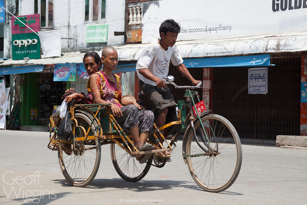 Tricycle taxi or sai kaa negotiates traffic in Sittwe, Myanmar