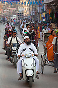 Muslim man wearing topi cap and white outfit driving motor scooter in street scene in city of Varanasi, Benares, Northern India