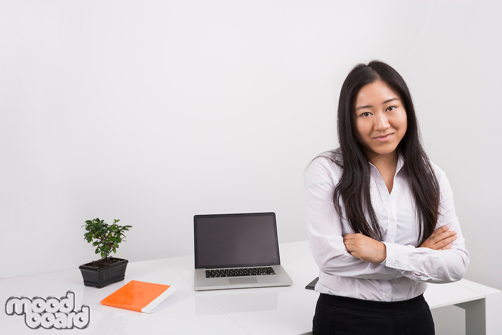 Portrait of confident businesswoman standing arms crossed in office