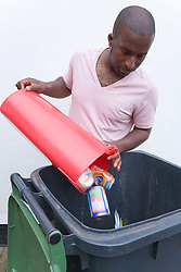Man putting tins and cans into recycling wheelie bin ready for collection,