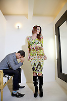 Young woman looking at self in mirror while man sitting on chair with hands on face