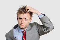 Portrait of confused businessman scratching head over colored background