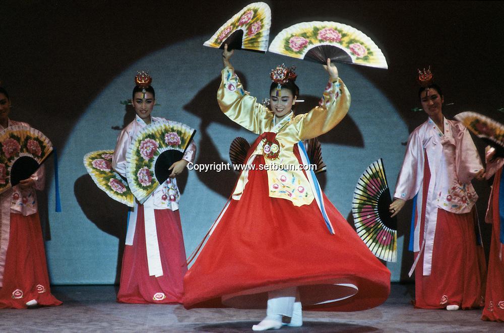 = Seoul, South Korea --- Women in traditional dress perform a fan dance in Seoul, South Korea. +